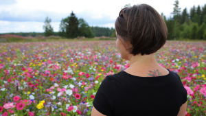 Miina Tuominen-Brinkas katsoo kukkaloistoa Brinkaksen tilalla Pyhtäällä.