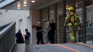 Palomies ja klinikan henkilökuntaa Naistenklinikan ulkopuolella Helsingissä 11. elokuuta 2019.