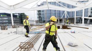 kaksi työmiestä rakennustyömaalla kantavat rautatankoa