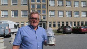 Mies pitää sellofaaniin pakattua peltipurkkia kädessään.