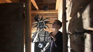 Anni Arffman taideteoksensa kanssa.