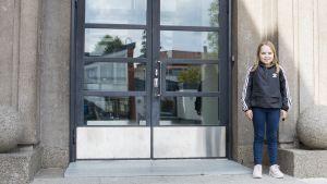 Aino Piironen koulunsa portailla.