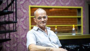 Kuopion Kaupunginteatterin johtaja Tommi Auvinen istuu Cabaret-musikaalin lavasteissa.