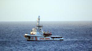 Hyväntekeväisyysalus Open Arms odottaa siirtolaisten kanssa pääsyä maihin Lampedusaan.