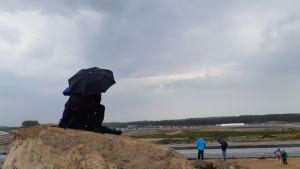 Ihmisiä sateenvarjon alla moottoriradan varressa.