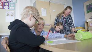 Luokanopettaja Malla Kärkkäinen neuvoo Dani Taskista kirjoitustehtävässä.