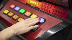 Rahapeliautomaatti lähikuvassa. Naisen käsi näppäimellä.
