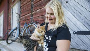 Hätäapukissalaa pyörittävä lapinlahtelainen Johanna Niskanen aitan portailla kissat sylissään.