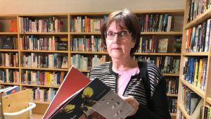nainen kirjahyllyn edessä selaamassa kirjaa