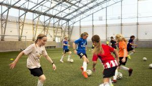 Tytöt pelaavat jalkapalloa.