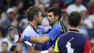 Stan Wawrinka ja Novak Djokovic halaavat serbialaisen luovutuksen jälkeen.