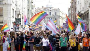 Suuri ihmisjoukko pride-marssilla liehuttaen sateenkaarilippuja.