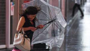 Nainen piteli sateenvarjostaan kiinni tuulten yltyessä Tokiossa 8. syyskuuta.