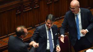 Italian pääministeri Giuseppe Conte (kuvassa keskellä) otti vastaan onnitteluja ministerikollegoilta Alfonso Bonafedeltä ja Federico D'Incalta luottamusäänestyksen jälkeen.