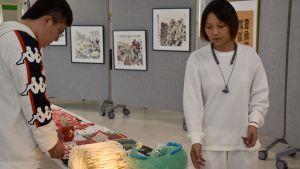 Kiinalainen mies ja nainen asettelevat koristeita pöydälle.