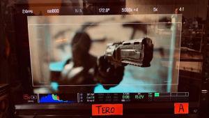 Elokuvan kuvauksissa monitorilla näkyy mies, joka osoittaa sivulle aseella.
