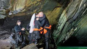 Hääpari suutelee vihkiseremonian päätteeksi sukelluspuvuissaan.