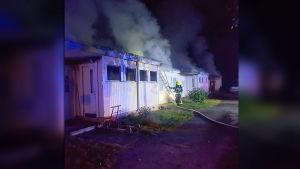 Palomies sammuttaa rakennuspaloa.