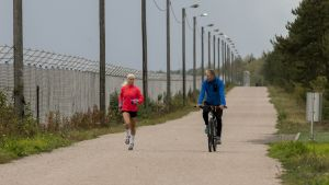 Alisa Vainiio punaisessa takissa juoksee Lappeenrannassa. Vieressä valmentaja Jarmo Viskari.