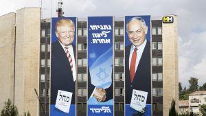 Bibi ja Trump kättelevät suuressa kerrostalon päätyyn pystytetyssä jusiteessa.