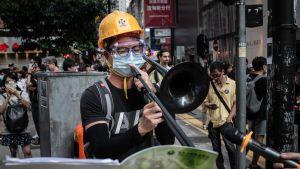 Mielenosoittaja soittaa pasuunalla protestihymiä syyskuun puolivälissä järjestetyssä demokratiamarssissa.