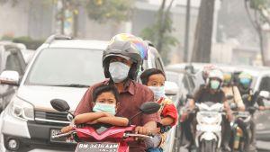 Hengityssuojaimilla varustautunut perhe ajamassa skootterilla Pekanbarussa, Indonesiassa.