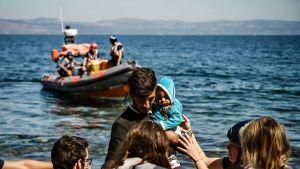 Pelastajat auttavat lesboksen saarelle saapuvia pakolaisia 16. syyskuuta.