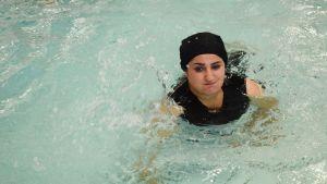 Iranilaistaustainen Sheida Mohammadi polskuttelee uimahallin altaassa.
