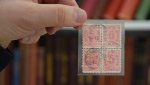 mies pitää sormissaan neljän postimerkin rypästä