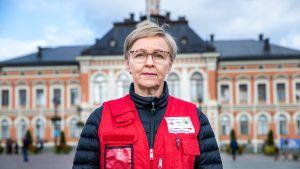 Vapaaehtoistyöntekijä Arja Savolainen Kuopion kaupungintalon edustalla.