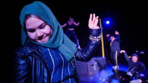 Maahanmuuttajanainen teatterilavalla esityksessä Selviytyjät.