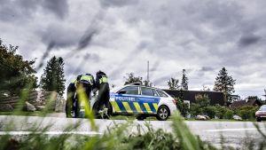 Poliisit etsivät Aivar Reheä tiistaina 24. syyskuuta. Kuvassa poliisit ovat ryhmittyneet poliisiauton etuosan ympärille neuvonpitoon.