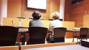 Kaksi naista istuu oikeussalissa.