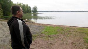 Mies seisoo rannalla ja katselee järven yli vastarannalle.