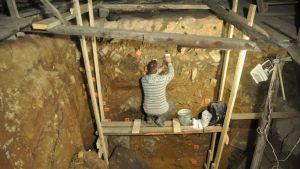 Telineellä kyyköttäjä tutkija kaivaa näytettä luolan pohjaan kaivetun kuopan seinämästä.
