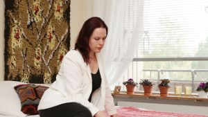 Johanna Kortesluoma lukee kirjettä sänkynsä päällä