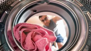 mies laittaa pyykkiä koneeseen, kuva otettu koneen sisältä