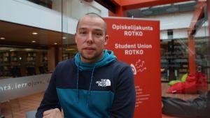 Tero Keskikallio poseeraa, opiskelijakunta Rotko esitteen edessä.
