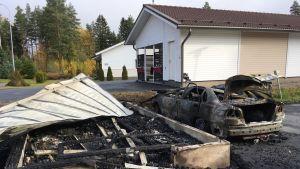 Tulipalossa tuhoutunut roskakatos ja auto.