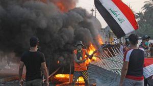 Mies heilutti Irakin lippua mielenosoituksessa Bagdadin Tayeranin aukiolla perjantaina.