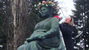 Kukkaseppele asetetaan Minna Canthin patsaalle. Lions Club Canth Kuopion presidentti Ulla Paksula seppelöi Minna Canthin patsaan Kuopiossa vuonna 2016.