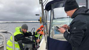 Kalastaja näyttää matkapuhelimestaan kalastuslupaa valvojalle.