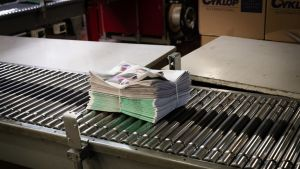 Yksinäinen sidottu sanomalehtinippu kulkee pitkin painolaitoksen rullalinjaa.