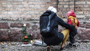 Nainen toi lapsensa kanssa kukkia synagogan edustalle 10. lokakuuta.