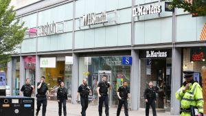 Poliiseja ostoskeskuksen ulkopuolella.