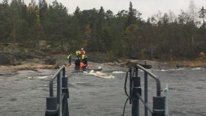 Kalastajaa pelastatetaan vedellä täyttyneestä veneestä.
