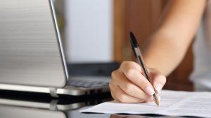 Nainen kirjoittaa toimistossa