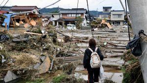 Nainen katsoo taifuunin aiheuttamaa tuhoa asuinalueella Naganossa.