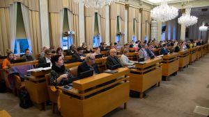 Turun kaupunginvaltuuston kokoussali. Valtuutetut istuvat pöytiensä ääressä.