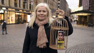 Tiina Jauhiainen pitää käsissään kultaista häkkiä, jonka sisällä on prinsessa Latifa Al Maktoumin kuva.